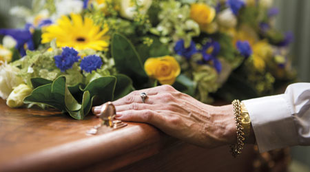 old person hand holding the coffin with arranged flowers on top
